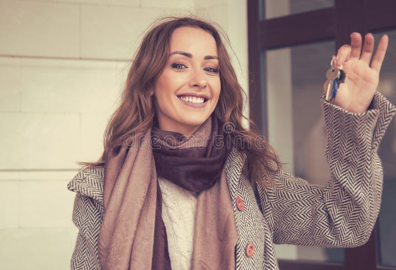 Chiavi felici della tenuta della donna dal suo nuovo appartamento immagine stock