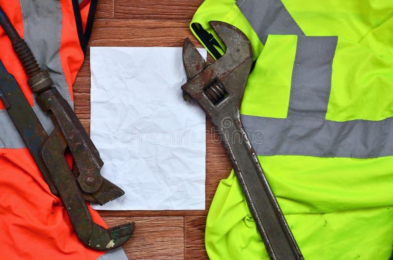 Chiavi inglesi e bugie della carta delle camice del lavoratore del segnale arancio e verde La natura morta si è associata con la  immagine stock