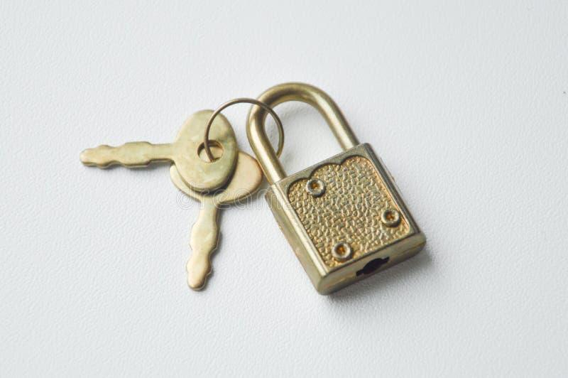 Chiavi metalliche e un piccolo lucchetto fotografia stock libera da diritti