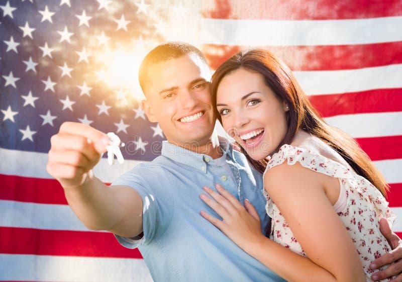 Chiavi militari della Camera della tenuta delle coppie davanti alla bandiera americana immagini stock libere da diritti
