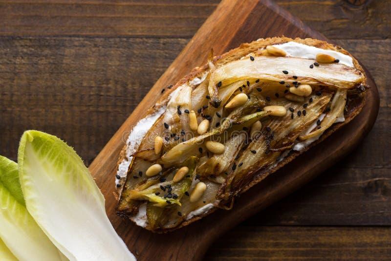 Chicória orgânica do assado na fatia do pão com pinhões e sésamo preto Alimento saud?vel org?nico imagem de stock royalty free