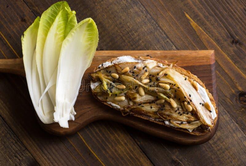 Chicória orgânica do assado na fatia do pão com pinhões e sésamo preto Alimento saud?vel org?nico fotografia de stock