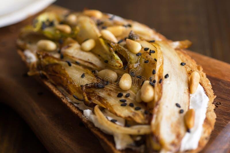 Chicória orgânica do assado na fatia do pão com pinhões e sésamo preto Alimento saud?vel org?nico foto de stock