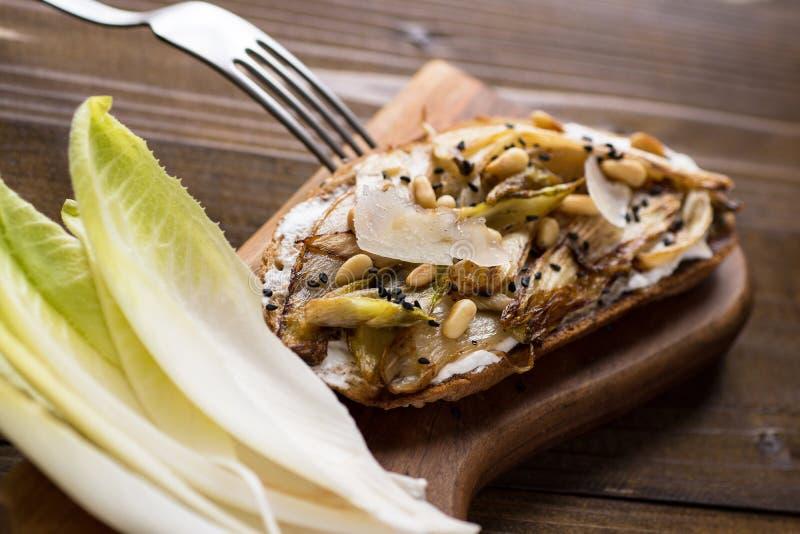 Chicória orgânica do assado na fatia do pão com pinhões e sésamo preto Alimento saud?vel org?nico fotografia de stock royalty free