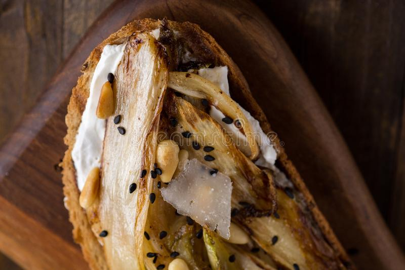 Chicória orgânica do assado na fatia do pão com pinhões e sésamo preto Alimento saud?vel org?nico foto de stock royalty free