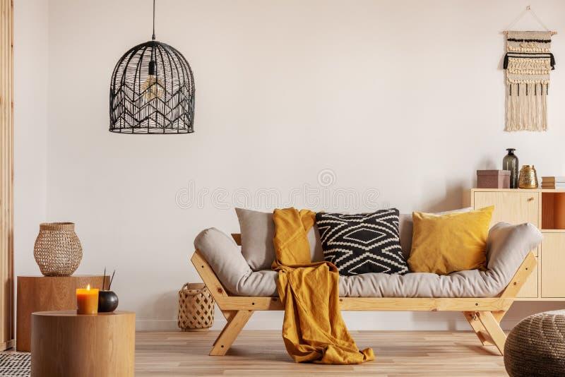 Chic black chandelier sobre sofá na sala de estar contemporânea imagem de stock