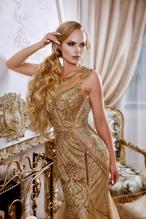 Beautiful girl in a long gold dress royalty free stock images
