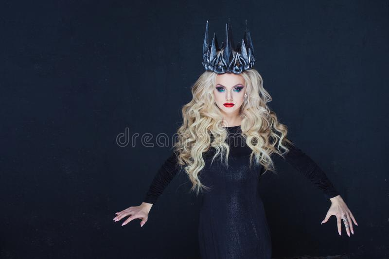 Chic Gothic Queen from a dark fairy tale. Young blonde woman in black with steel crown on her head royalty free stock images