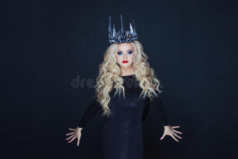 Chic Gothic Queen from a dark fairy tale. Young blonde woman in black with steel crown on her head. Mystical image royalty free stock photography