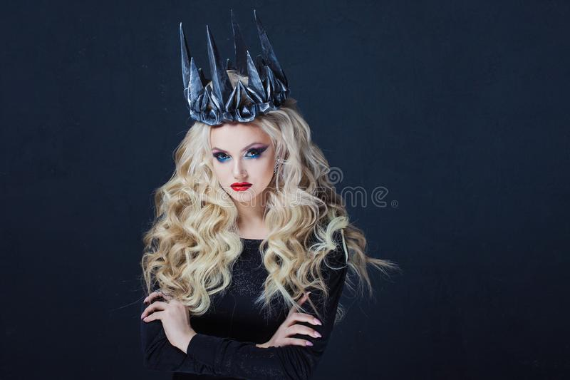 Chic Gothic Queen from a dark fairy tale. Young blonde woman in black with steel crown on her head royalty free stock image