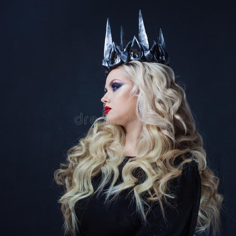 Chic Gothic Queen from a dark fairy tale. Young blonde woman in black with steel crown on her head. Mystical image stock photo