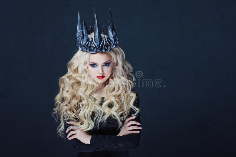 Chic Gothic Queen from a dark fairy tale. Young blonde woman in black with steel crown on her head royalty free stock photography