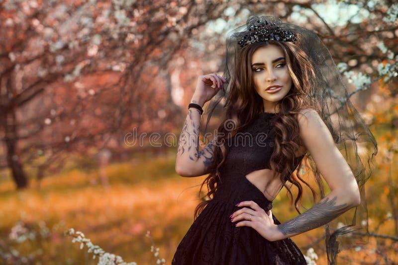 Chic mörker-haired tatuerat bära för ung kvinna snör åt klänningen och svärtar juvelkronan med skyler anseende i höstträdgården royaltyfri bild
