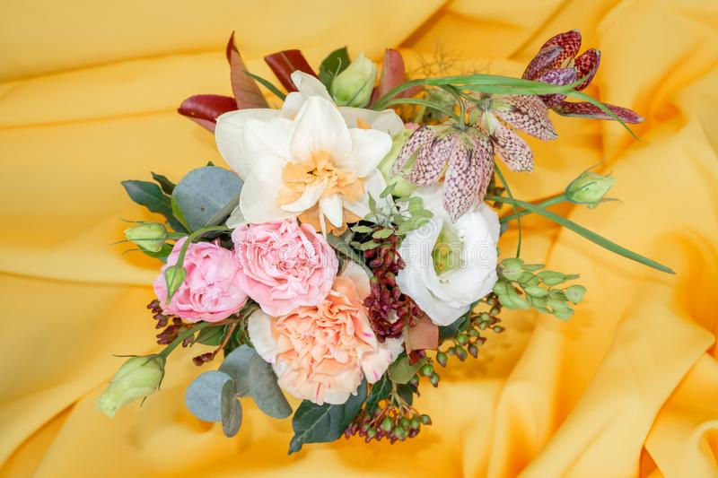Chic mini bouquet of roses, daffodils and other flowers on a yellow background stock photo