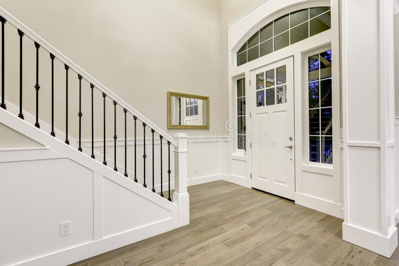 Chic white entryway design accented with high ceiling stock image