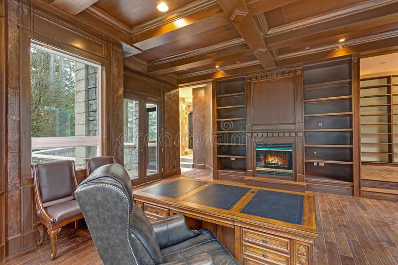 Chic Wood Paneled Home office features coffered ceiling. Over gorgeous carved wood antique desk facing a fireplace with Built in wooden book shelves royalty free stock image