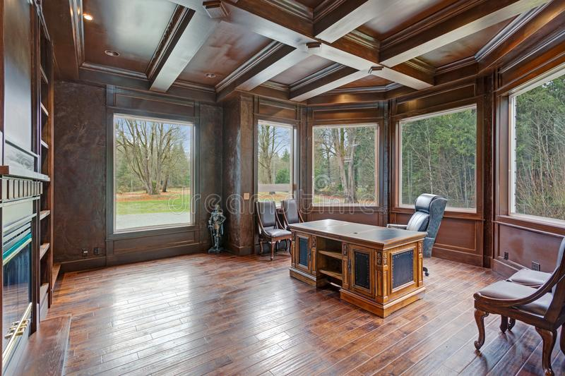 Chic Wood Paneled Home office features coffered ceiling. Over gorgeous carved wood antique desk placed in the centre of the room atop hardwood floor stock photo