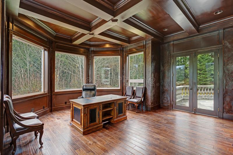 Chic Wood Paneled Home office features coffered ceiling. Over gorgeous carved wood antique desk placed in the centre of the room atop hardwood floor royalty free stock photography