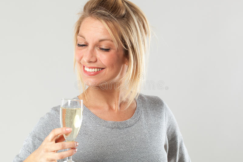 Chic young blond woman enjoying drinking flute of bubbly wine. Female drinker - chic beautiful young blond woman enjoying drinking a flute of bubbly wine to royalty free stock photography