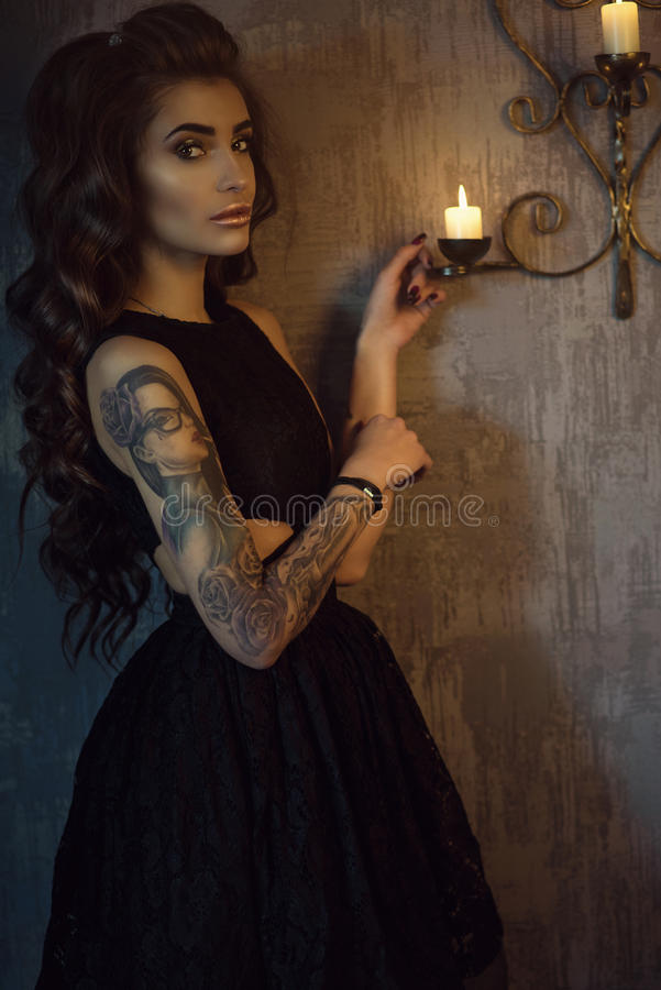 Chic young tattooed woman with luxurious long wavy silky hair standing in the dark shabby room at the burning candles stock photo