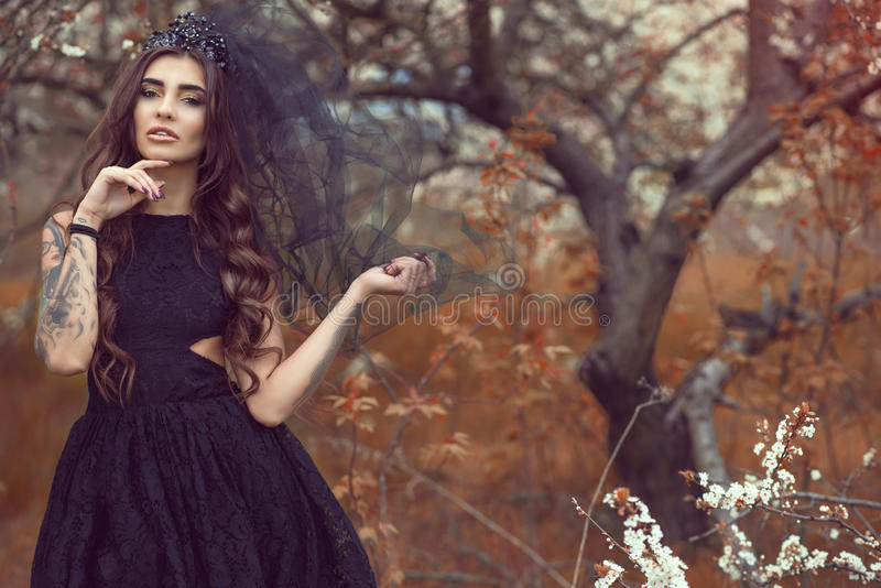 Chic young woman with perfect make up wearing lace dress and black jewel crown with veil standing in the abandoned garden royalty free stock photos