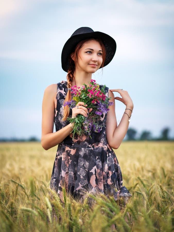 Chica atractiva y agradable con un ramo de flores de colores en las manos. Mujer joven respira en el aroma de las plantas en el ca imágenes de archivo libres de regalías