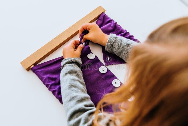 Chica bastión montessori para desarrollar la destreza de sus dedos fotografía de archivo libre de regalías