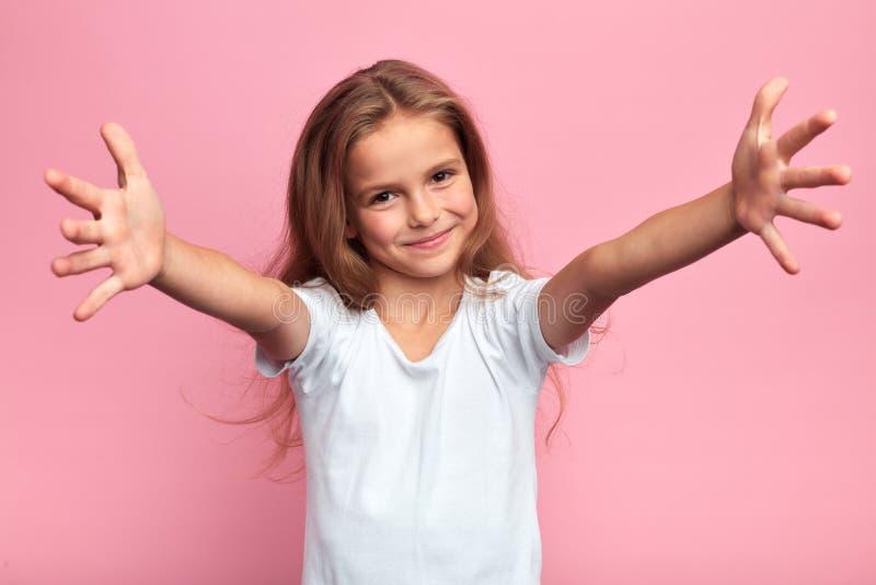 Chica con camiseta blanca con los brazos abiertos para abrazar a su familia, fotografía de archivo