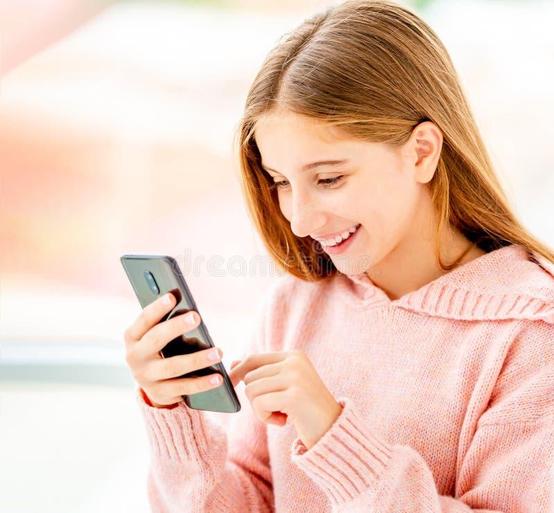 Chica con teléfono de media vuelta fotografía de archivo libre de regalías