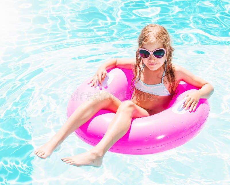 Chica en el anillo inflable en la piscina fotografía de archivo libre de regalías