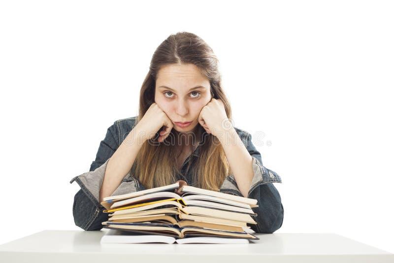 Chica joven aburrida del estudiante con los libros imagen de archivo