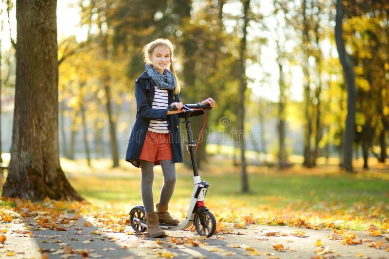 Chica joven adorable que monta su vespa en un parque de la ciudad en la tarde soleada del otoño Niño bonito del preadolescente qu imagen de archivo