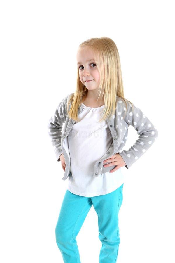 Chica joven adorable que se coloca con sus manos en sus caderas imagen de archivo
