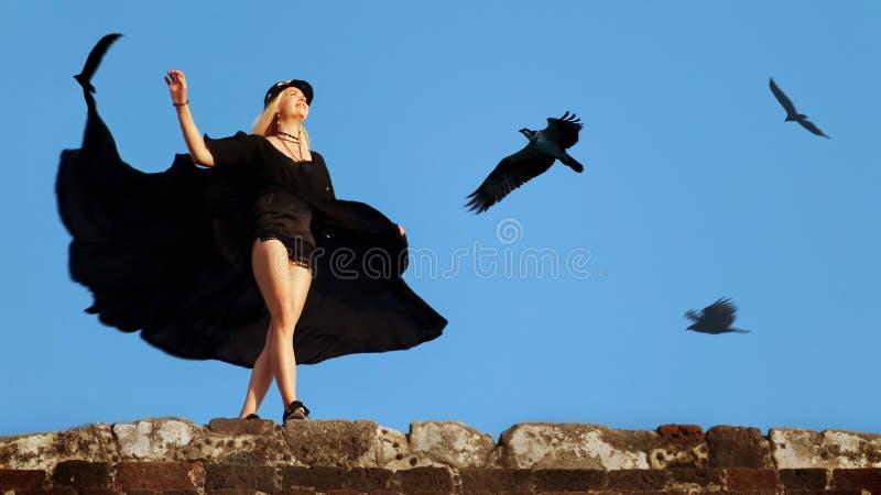 Chica joven agraciada en un vestido negro que vuela y pantalones cortos contra el cielo azul y las águilas que vuelan imágenes de archivo libres de regalías