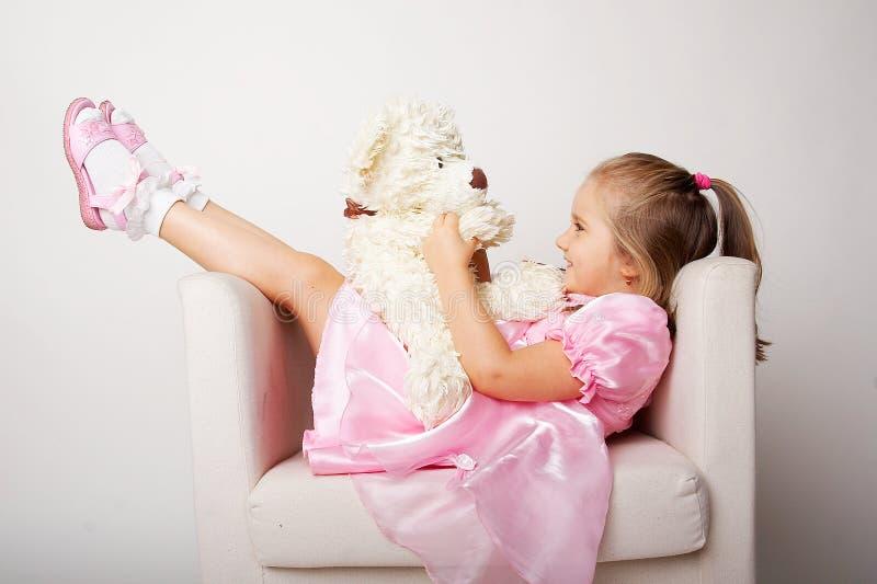 Chica joven agradable en color de rosa en fondo ligero imagenes de archivo