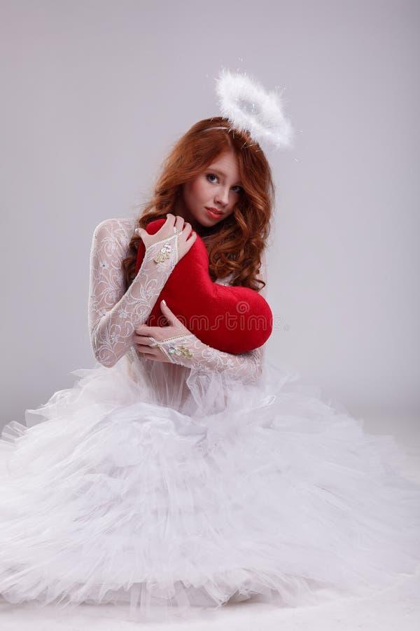 Chica joven agradable vestida como ángel que presenta con el corazón fotografía de archivo libre de regalías