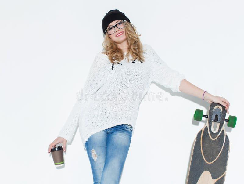 Chica joven alegre de moda de Bautiful en un suéter blanco con un vidrio de café y de longboard que presentan cerca de la pared b fotos de archivo libres de regalías