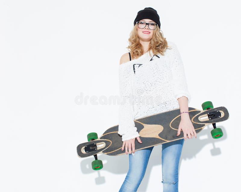 Chica joven alegre de moda de Bautiful en un suéter y un longboard blancos que presentan cerca de la pared blanca en el estudio imagen de archivo