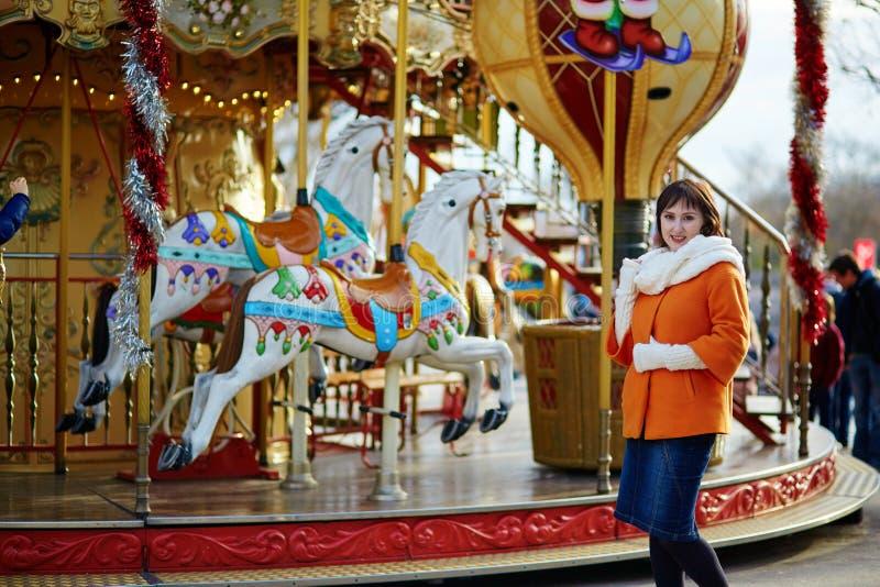 Chica joven alegre en un mercado de la Navidad en París foto de archivo