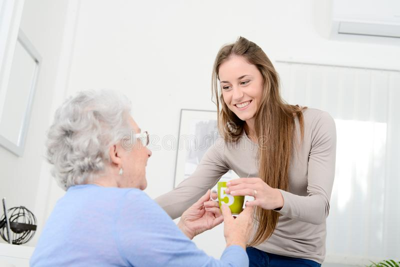 Chica joven alegre que toma cuidado de la vieja mujer mayor en su hogar imágenes de archivo libres de regalías