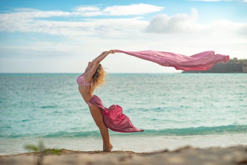 Chica joven apta y deportiva que presenta en una playa con la seda que vuela rosada fotografía de archivo