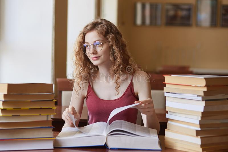 Chica joven apuesta positiva que tiene la expresión facial agradable, lentes superiores y elegantes rojas que llevan, tocando el  foto de archivo libre de regalías