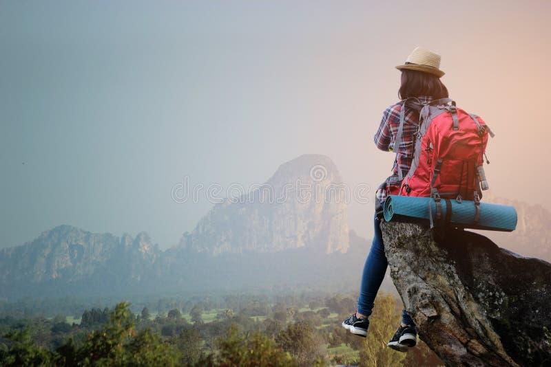Chica joven asiática del inconformista con la mochila que disfruta de puesta del sol en la montaña máxima Concepto de la aventura fotografía de archivo libre de regalías