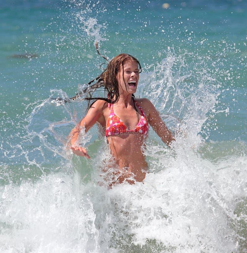 Chica joven atractiva atractiva que es salpicada por la onda fría en el SE imagen de archivo libre de regalías