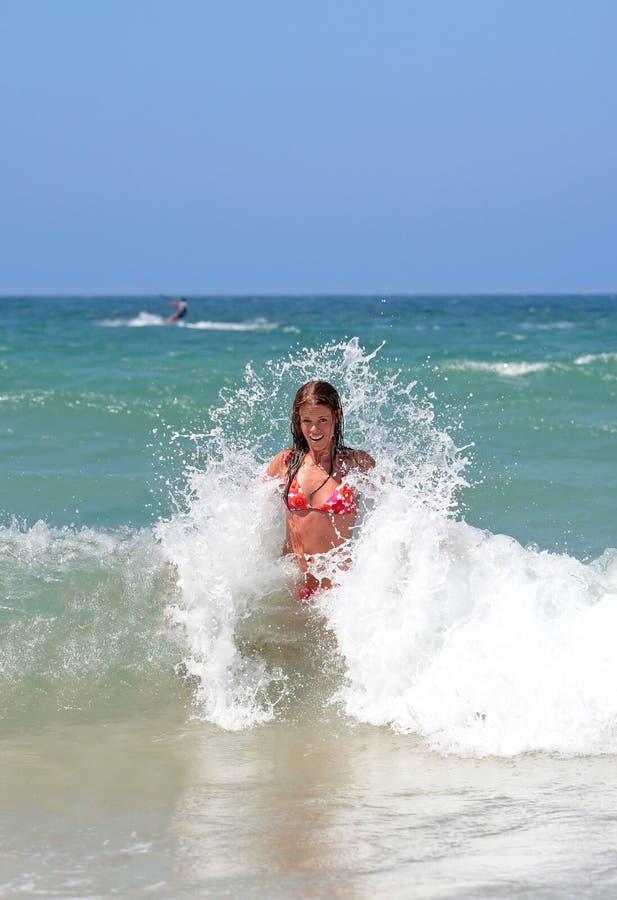 Chica joven atractiva atractiva que es salpicada por la onda fría en el SE imágenes de archivo libres de regalías