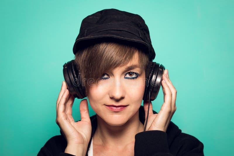 Chica joven atractiva con los auriculares que miran la cámara y la sonrisa fotos de archivo libres de regalías