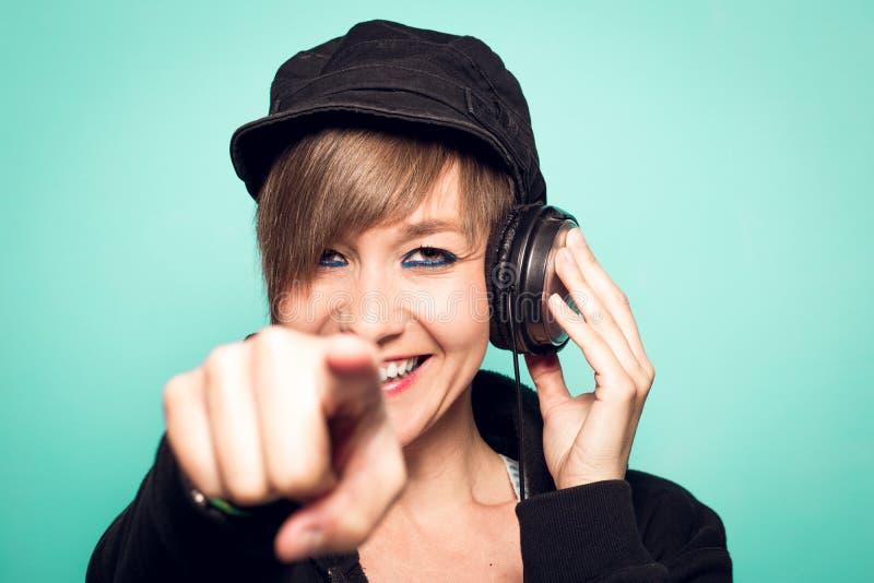 Chica joven atractiva con los auriculares que miran la cámara y la sonrisa imagen de archivo libre de regalías
