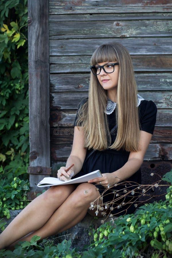 Chica joven atractiva con un álbum para dibujar fotografía de archivo