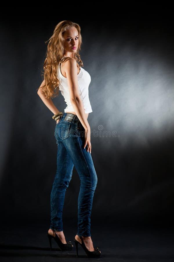 Chica joven atractiva en la camiseta y los pantalones vaqueros blancos fotos de archivo