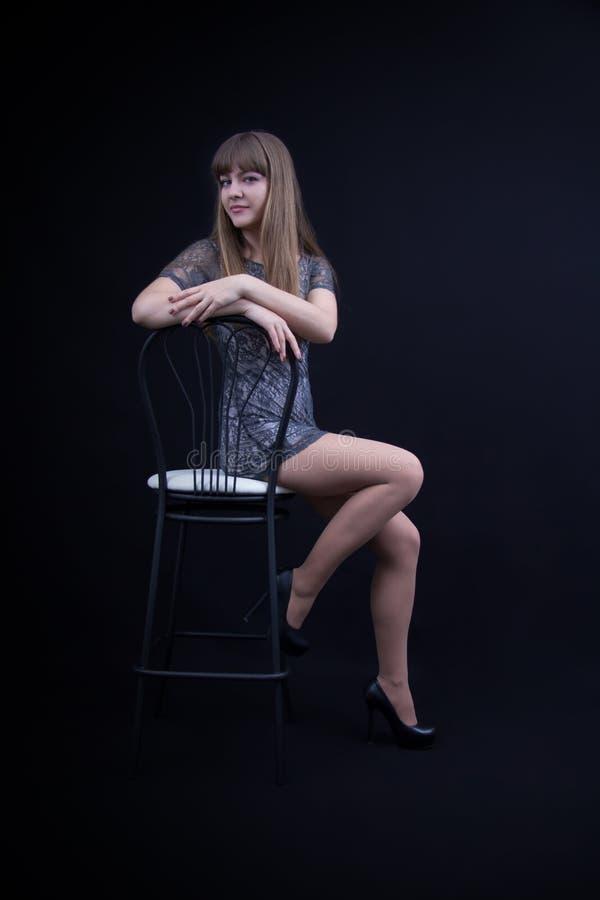 Chica joven atractiva en una silla imagen de archivo libre de regalías